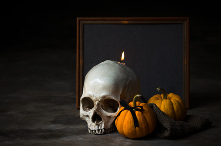 pumkin: still life halloween human skull with yellow pumkin and candle Stock Photo