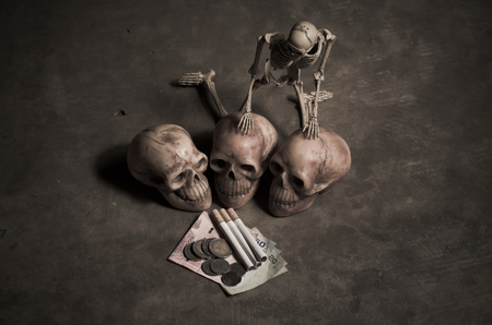 losing money: still life style of skull with losing money of cigarette Stock Photo