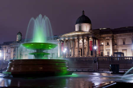 a green lighted fountain on trafalgar square iin front of the national gallery illuminated