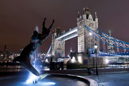 the fountain with a statue of a girl and a dolphin, illuminated, in front of the tower bridge