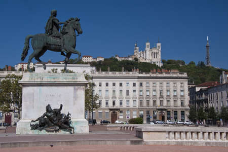 view of the equestrian statue of louis xiv and the basilica of notre dame de fourviere from place bellecour, in the center of lyon Standard-Bild