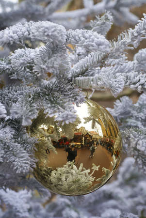 reflection of the christmas market of Colmar in Alsace, in a ball hanging from a white christmas tree photo