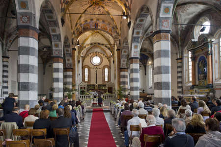 catholic wedding: Couple seen from the bottom of the aisle of a romanic church, while theyre getting married