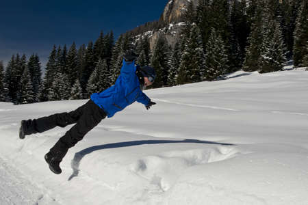 fassa: Young boy playing an jumping into the snow in val di fassa, in the dolomites
