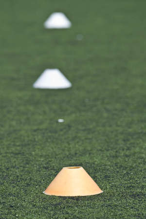 delimit: Yellow cone on a soccer field for training