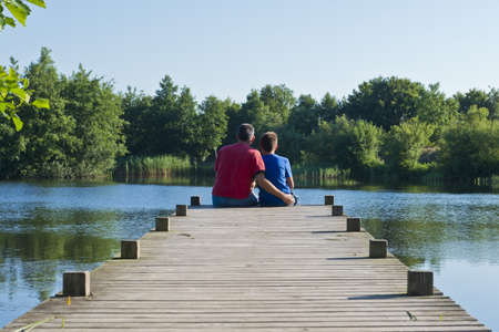 sitted: Father and son sitted on a wooden pier on a quiet blue pond in Denmark Stock Photo
