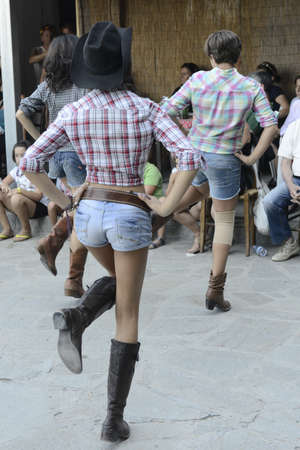 Girls dressed like cowgirls dancing