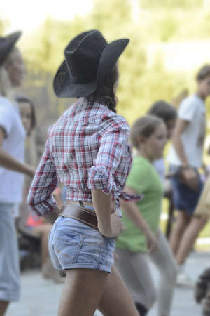 Girl dressed like cowgirl, with denim shorts and cowboy hat,  dancing Redakční