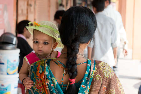 JAIPUR, INDIA - 20 OCTOBER 2013 - Unidentified indian mom holding a little girl on her arm, walking in the Jaipur Market