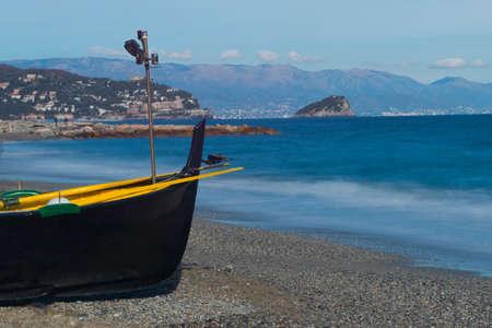 Black boat on the beach of Noli, on the Riviera ligure, Italy Standard-Bild