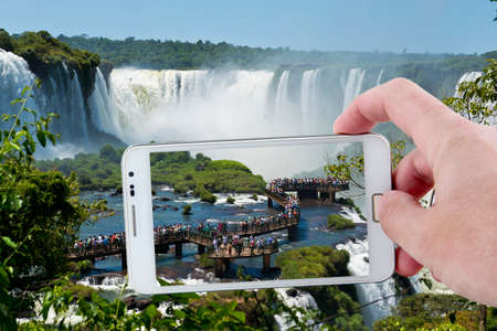 natural wonders: Taking a picture at the footbridge over the magnificent garganta del diablo at the iguazu falls, one of the seven natural wonders of the world Editorial