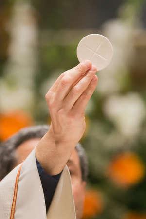 sacerdote: El pan sagrado de la comunión en la misa Editorial