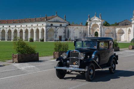 Old vintage automobile crossing Villa Manin in Codroipo.