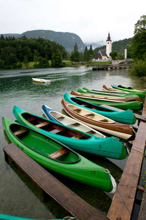 Canoes facing the church dedicated to John the Baptist in Ribcev Laz on the Bohinj Lake, in Slovenia Editorial