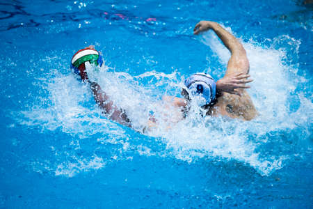 waterpolo: Throw and game action in a swimming pool, during a waterpolo match Editorial