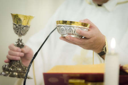 goblet: Priest celebrating the communion with goblet and holy bread Stock Photo