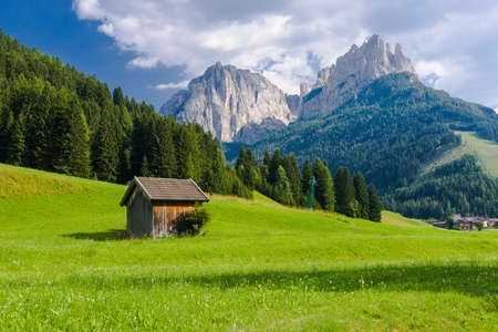 mountain hut: Summer view over fields and mountain hut in the Dolomites of the Fassa  Valley Stock Photo