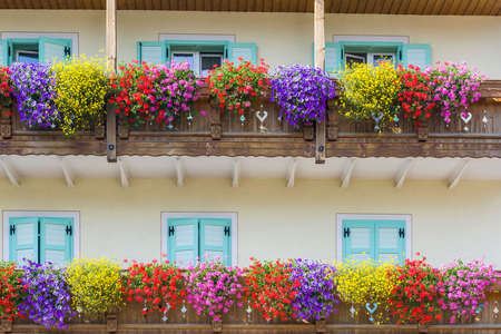 fassa: Colorful wood balcony full of flowers in bloom in Fassa Valley Stock Photo