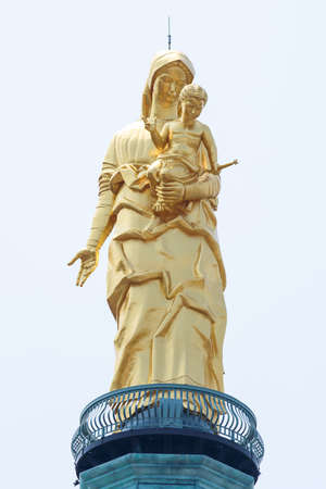 Gold statue of Virgin and Child on the top the shrine of our lady of the guard in Tortona