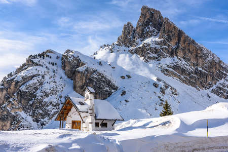 Little church in the snow  under Sass de Stria at Falzarego Pass in the Dolomites