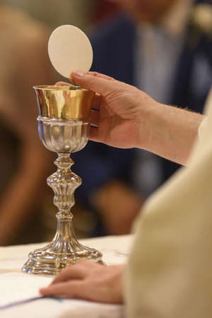 The sacred gesture during the christian mass: showing the holy bread Zdjęcie Seryjne - 98402704