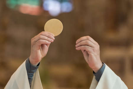 Minister showing the holy bread during the rite of the Holy Communion during the catholic mass