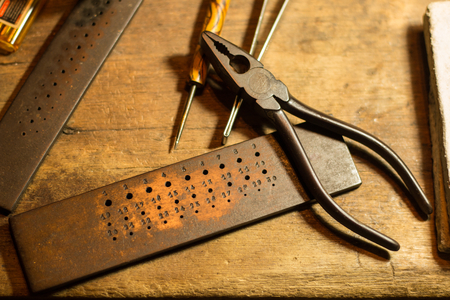 craft tool for goldsmith work in workshop . steel ruler of measure gold size on wooden table . Archivio Fotografico