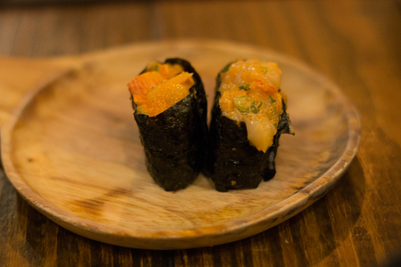 Scallop or shell sushi and crab seaweed wrap on wood dish , table . Japanese healthy fresh food .