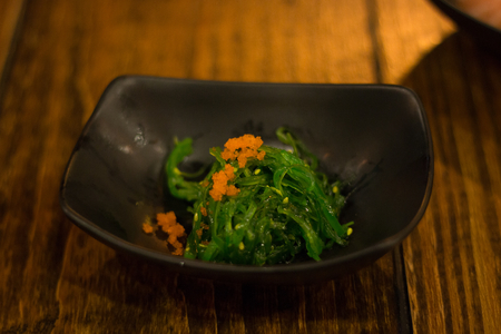organic seaweed or alga is a vegetable grass food in black dish on wood table . Japanese salad .