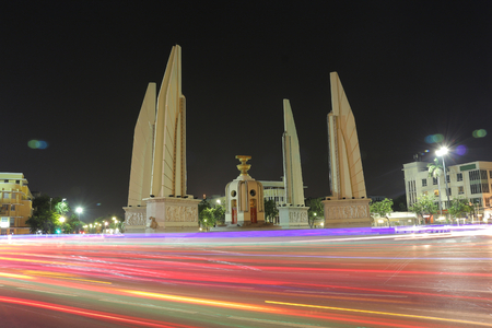 Democracy monument is circular traffic landmark at Bangkok Thailand . architecture in history . slow motion of light on street at night .
