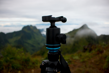 Tripod and landscape mountain view at background . outdoor picture and video working . equipment for dslr traveller . Banco de Imagens