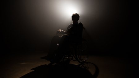Silhouette dark man on wheelchair at mystery stage . disabled adult male sitting  in shadow . Stock Photo