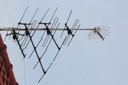 tv antenna above roof at home , receiver communication data with blue sky