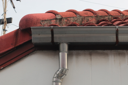 stainless steel pipe gutter at corner roof with sky .