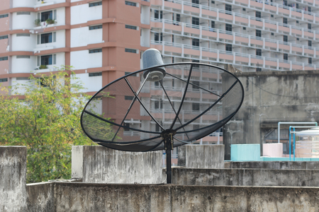 black satellite dish and tv antenna at old village , parabolic digital receiver for communication data on roof .