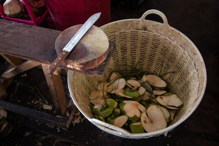 coconut and peel in basket , knife on wooden table at workplace in market