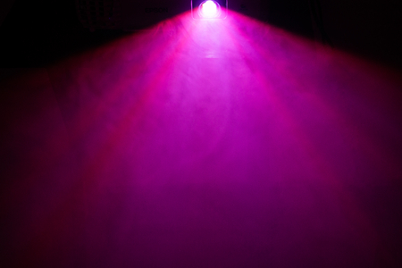 beautiful purple color wide lens projector with light beam for movie and cinema at night . smoke texture spotlight . effects screening for multimedia . black background .
