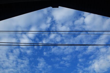 silhouette wires line and house roof , blue sky and white alto cumulus cloudy . Stock Photo