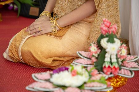 close up gold wedding ring , dress and accessories of beautiful bridal Thai style .