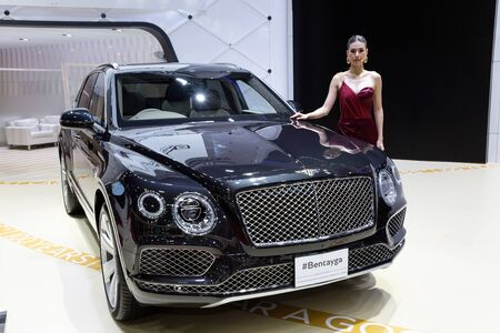 Nonthaburi , Thailand - April 3, 2019: The New Bentley Bentayga luxury sport car and beautiful pretty girl presented in motor expo Thailand . Редакционное