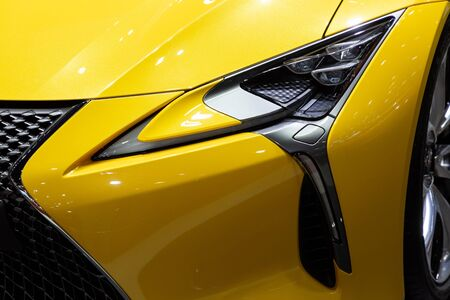 Thailand - April 3, 2019: close up front view headlight of Lexus LC 500 yellow color car presented in motor show Thailand .