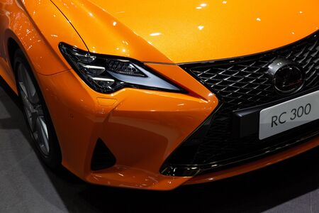 Thailand - April 3, 2019: close up front view headlight of Lexus RC 300 orange color car presented in motor show Thailand .