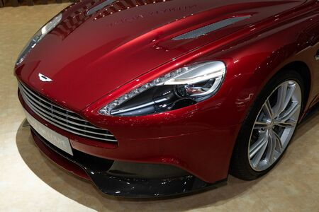 Thailand - April 3, 2019: close up front view headlight of Aston Martin vanquish coupe red color luxury car presented in motor show Thailand . Editöryel