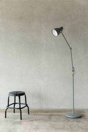 gray electricity lamp post and black chair interior furniture , bare cement wall minimal background . Reklamní fotografie