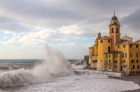 Old church with rough sea and big waves in Camogli, Genoa, (Genova), Italy