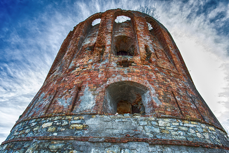 Isolated old brick tower under a blue cloudy sky