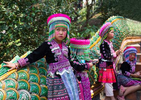 Three unidentified Akha children pose for tourist photos at Wat Phratat Doi Suthep on February 18, 2017 in Chiang Mai, Thailand.