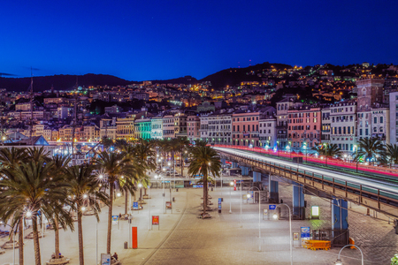 Traffic light trails in Genoa causeway, with skyline of the historic city center buildings Editorial