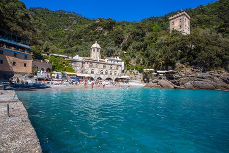 San Fruttuoso di Camogli, Ligurian coast, Genoa province, with its ancient Abbaey, the beach and tourists.