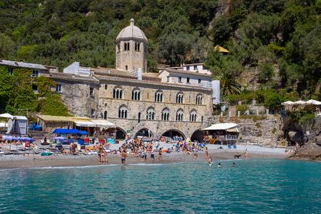 San Fruttuoso di Camogli, Ligurian coast, Genoa province, with its ancient Abbaey, the beach and tourists. Italy.
